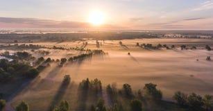 Le lever de soleil aérien avec le brouillard à l'arbre complète dans la campagne rurale Image libre de droits