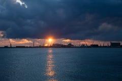 Le lever de soleil au-dessus de la mer avec menacer opacifie à l'arrière-plan du port commercial Photo libre de droits