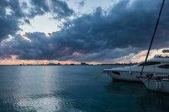Le lever de soleil au-dessus de la mer avec menacer opacifie à l'arrière-plan du port commercial Photographie stock