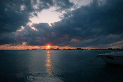 Le lever de soleil au-dessus de la mer avec menacer opacifie à l'arrière-plan du port commercial Photos libres de droits