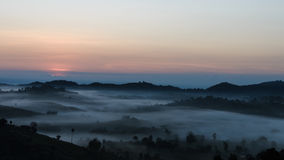 Le lever de soleil avec un brouillard en hiver images libres de droits