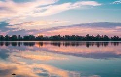 Le lever de soleil coloré de matin se reflétant dans le lac clair arrose Images stock