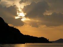 Le lever de soleil coloré sous les montagnes et la mer Image libre de droits