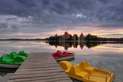 Le lever de soleil d'une manière fantastique ardent d'été au-dessus du château d'île de Trakai en Lithuanie, avec de l'eau une be Photo stock