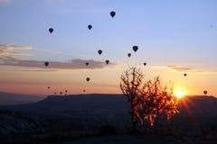 Le lever de soleil dans les montagnes avec beaucoup de ballons chauds d'air dans le ciel Photographie stock