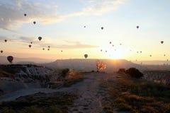 Le lever de soleil dans les montagnes avec beaucoup de ballons chauds d'air dans le ciel Photos stock