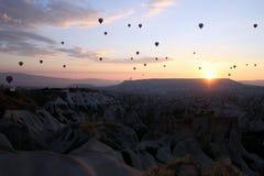 Le lever de soleil dans les montagnes avec beaucoup de ballons chauds d'air dans le ciel photo stock