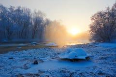 Le lever de soleil gelé de rivière et de neige et de cristaux de glace Photos stock