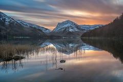 Le lever de soleil vibrant d'hiver avec la neige sur Buttermere abat dans le secteur de lac images libres de droits