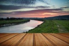 Le lever de soleil vibrant renversant s'est reflété en rivière calme avec le pl en bois photographie stock