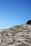 Le lichen a couvert la roche contre le ciel bleu photo libre de droits