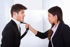 Le lien de Holding Businessman fâché de femme d'affaires Photographie stock