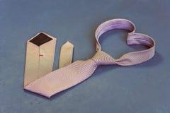 Le lien rose est attaché sous forme de coeur sur un fond gris Photographie stock