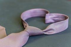 Le lien rose est attaché sous forme de coeur sur un fond gris T Images libres de droits