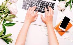 Le lieu de travail avec la femelle d'ordinateur portable remet des pivoines de stylo de carnet de téléphone portable Photos stock