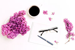 Le lieu de travail avec la tasse du lilas en verre de stylo de journal intime de café fleurit Photographie stock
