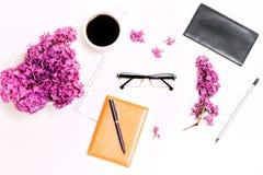 Le lieu de travail avec le lilas en verre de crayon de stylo de laiterie de café de tasse fleurit Photographie stock
