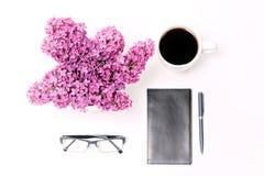 Le lieu de travail avec le lilas en verre de stylo de journal intime de café de tasse fleurit Images libres de droits