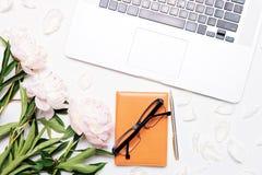 Le lieu de travail avec le stylo et la pivoine de carnet en verre d'ordinateur portable fleurit Images stock