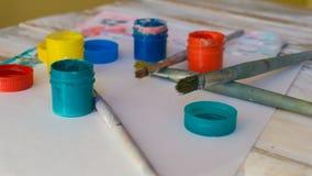 Le lieu de travail de l'artiste : peintures d'aquarelle, pinceaux, feuilles de livre blanc, palette de couleurs et peinture non f photo stock