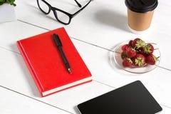 Le lieu de travail minimalistic élégant avec le comprimé et le carnet et les verres dans l'appartement étendent le style Fond bla Photographie stock libre de droits