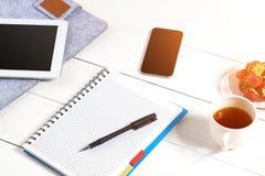 Le lieu de travail minimalistic élégant avec le comprimé et le carnet et les verres dans l'appartement étendent le style Fond bla Photo stock