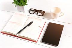 Le lieu de travail minimalistic élégant avec le comprimé et le carnet et les verres dans l'appartement étendent le style Fond bla Photos libres de droits