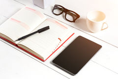 Le lieu de travail minimalistic élégant avec le comprimé et le carnet et les verres dans l'appartement étendent le style Fond bla Photo libre de droits