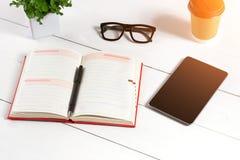Le lieu de travail minimalistic élégant avec le comprimé et le carnet et les verres dans l'appartement étendent le style Fond bla Photographie stock