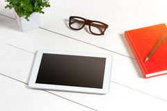 Le lieu de travail minimalistic élégant avec le comprimé et le carnet et les verres dans l'appartement étendent le style Fond bla Image libre de droits