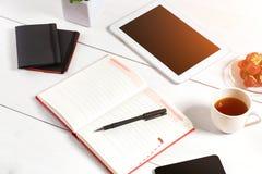 Le lieu de travail minimalistic élégant avec le comprimé et le carnet et les verres dans l'appartement étendent le style Fond bla Images stock