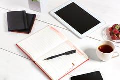 Le lieu de travail minimalistic élégant avec le comprimé et le carnet et les verres dans l'appartement étendent le style Fond bla Image stock