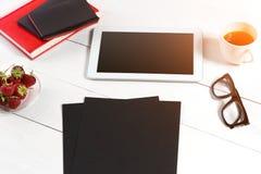 Le lieu de travail minimalistic élégant avec le comprimé et le carnet et les verres dans l'appartement étendent le style Fond bla Photos stock