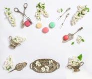 Le lilas blanc de configuration plate fleurit la nourriture de bonbon à gâteaux de macaron photographie stock libre de droits