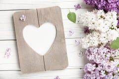 Le lilas fleurit le fond avec le cadre en forme de coeur vide de photo photo libre de droits