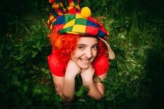 Le lilla flickan i clownperuk Arkivfoton