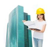 Le lilla flickan i hardhat med skrivplattan Arkivbild