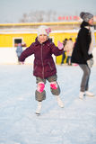 Le lilla flickan i knäblock som åker skridskor på isbanan fotografering för bildbyråer