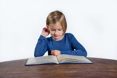 Le lilla flickan med en bok på en vit bakgrund Royaltyfri Bild