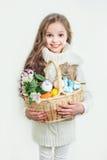 Le lilla flickan med korgen som är full av färgrika easter ägg Arkivbild