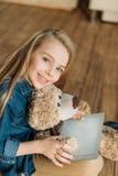 Le lilla flickan med nallebjörnen som rymmer den digitala minnestavlan Royaltyfri Foto