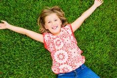 Le lilla flickan som ligger på grönt gräs royaltyfria bilder