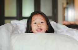 Le lilla flickan som ligger under en vit filt på sängen fotografering för bildbyråer