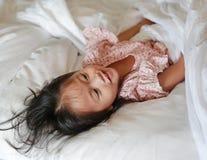Le lilla flickan som ligger under en vit filt p? s?ngen royaltyfri bild