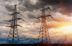 Le linee ad alta tensione di trasmissione dell'elettricità sono nel campo e nel cielo tempestoso con i raggi del sole Fotografie Stock