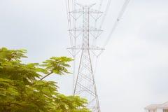 Le linee di trasmissione di Electric Power sopra gli alberi e residenziali sono fotografie stock libere da diritti
