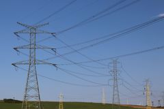Le linee elettriche ad alta tensione attraversano la stazione elettrica del mestnost collinoso di estate sotto il cielo aperto L' Fotografie Stock Libere da Diritti