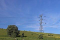 Le linee elettriche ad alta tensione attraversano la stazione elettrica del mestnost collinoso di estate sotto il cielo aperto L' Immagini Stock Libere da Diritti
