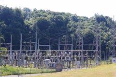 Le linee elettriche ad alta tensione attraversano la stazione elettrica del mestnost collinoso di estate sotto il cielo aperto L' Fotografia Stock Libera da Diritti