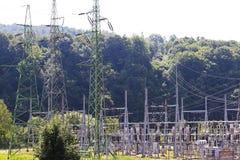 Le linee elettriche ad alta tensione attraversano la stazione elettrica del mestnost collinoso di estate sotto il cielo aperto L' Immagini Stock